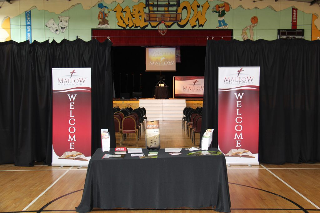 Entrance to Mallow Bible Fellowship. Welcome table and banners are placed in front of a curtain which divides the main hall in half. In the background, you see through the curtains to the stage.